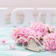 Pink flowers, wooden word love and decorative heart   on turquoise wooden background against white wall. Selective focus.